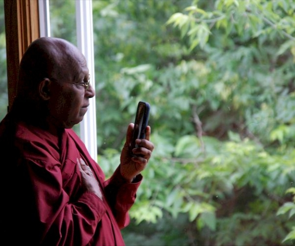 Monk taking a picture of the lake from the dinner hall at the Metta Meditation Center