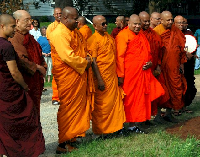 Monks watching the unveiling the Metta Meditation Center sign
