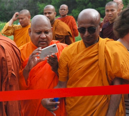 Monk taking photo at the ribbon cutting ceremony.
