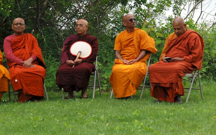 Monks by the lake during the dedication ceremony at the Metta Meditation Center