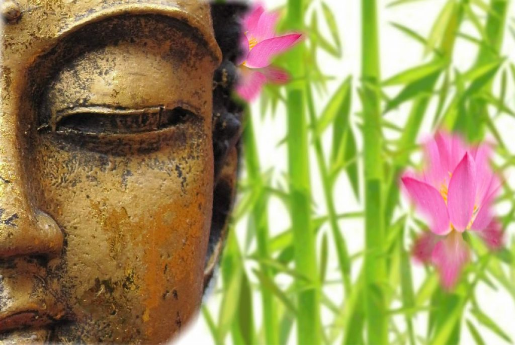 Buddha with bamboo and pink flowers in background